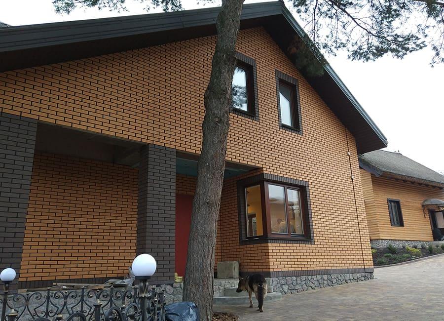 Коричневі дерев'яні вікна в цегляному фасаді